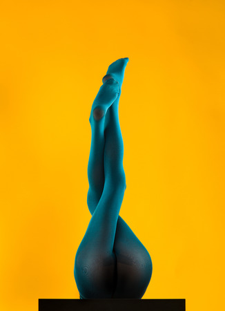 woman wearing blue stockings lying on her back with her legs up, crossed, on yellow background photo