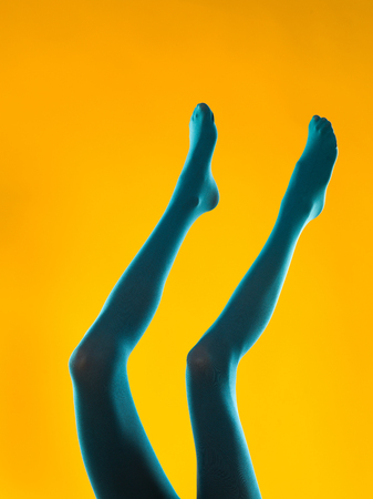 cropped view of woman legs in blue stockings on yellow background Stock Photo - 22877523