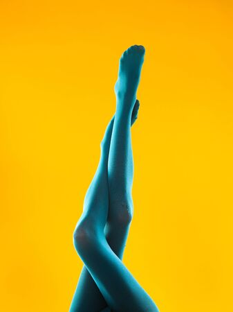 cropped view of woman holding her legs crossed in blue pantyhose, on yellow background Stock Photo - 22877527