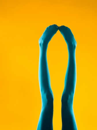 cropped front view of female legs in blue stockings on yellow background Stock Photo - 22877526