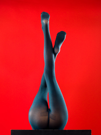 woman wearing pantyhose lying on her back with her feet up on red background
