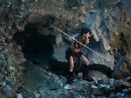 caucasian woman dressed as a caveman holding a spear, getting ready for hunting, close to a rocky cave