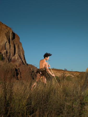 primitivism: woman dressed as a caveman hunting with a spear in nature
