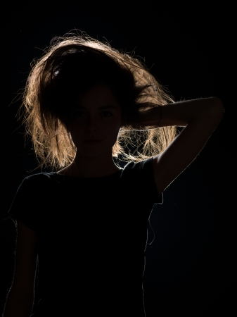 messed up: front view of woman in black shadow with messed up hair, on black background Stock Photo