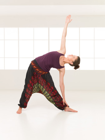 introversion: advanced yoga posture, demonstrated by colorful girl, studio indor window background