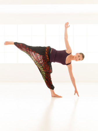 chandrasana: yoga posture demonstration by young woman, dressed colorful in studio