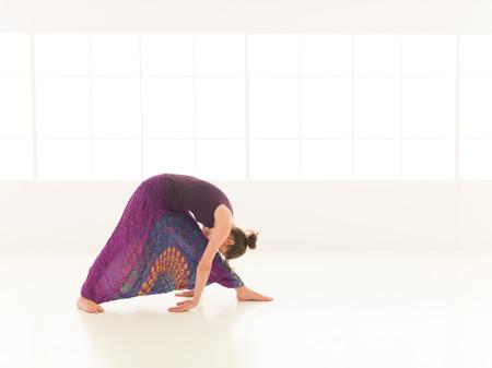 iluminated: vista lateral de la mujer joven en postura de yoga, cara obscuredm vestido colorido, backgrond ventana iluminated