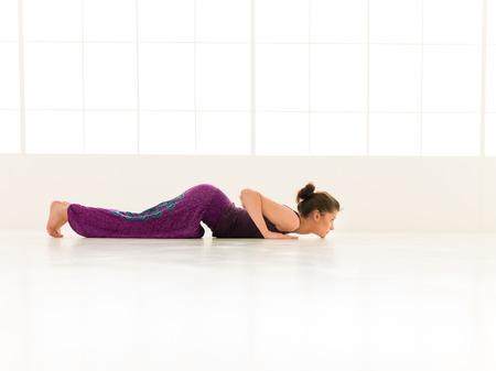iluminated: Chica joven que demuestra yoga avanzada pose, la vista de todo el cuerpo, vestido colorido, backgrond ventana iluminated