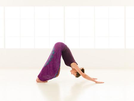 iluminated: mujer joven sentada en estirar pose de yoga, vestido colorido, backgrond ventana iluminated