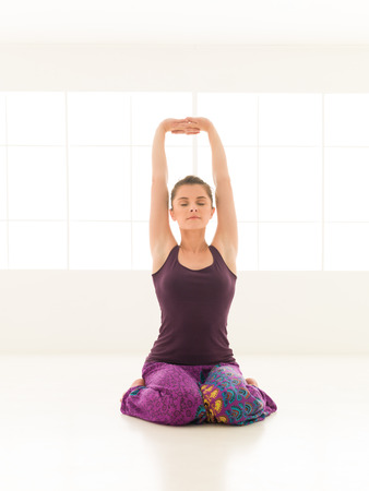 iluminated: hermosa mujer joven sentada en el hatha-yoga pose, fondo de la ventana iluminated