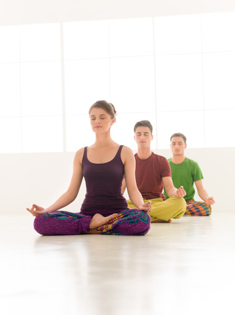 stretching exercise: Three young people a woman and two men practice yoga class stand in line