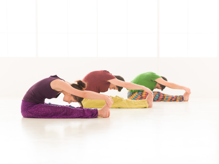patience: Three young people a woman and two men practice yoga in class on background window colorful