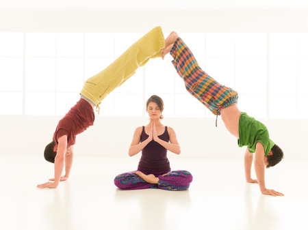 meditation help: Three young people a woman and two men practice yoga partner in class on background window