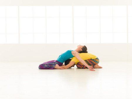 two people a man and a woman doing yoga partners in a white gym