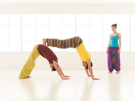acrobacia: personas vestidas con colores vibrantes realizan movimientos de yoga