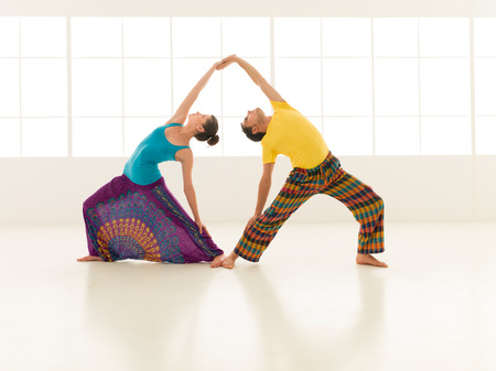 beautiful woman with a handsome man dressed in vibrant colors are partners yoga in white gym photo