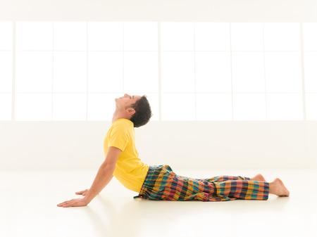 bhujangasana: Colorful dressed male repeating bujangasana cobra pose yoga exercises in a white room with window background