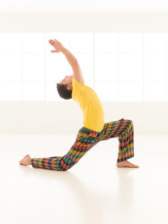 virabhadrasana: Colorful dressed male repeating Virabhadrasana yoga exercises in a white room with window background