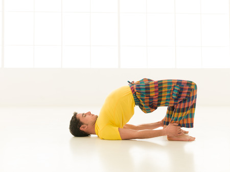 dhanurasana: Colorful dressed male repeating Dhanurasana yoga exercises in a white room with window background
