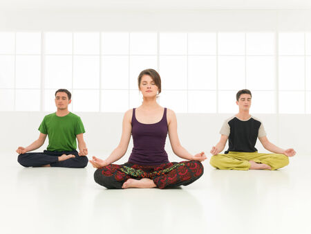Young woman with two boys on a course of yoga in beautiful clean gym photo