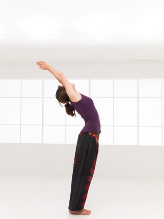 chandrasana: back bent yoga pose, demonstrated by young woman, dreesed colorful, window background