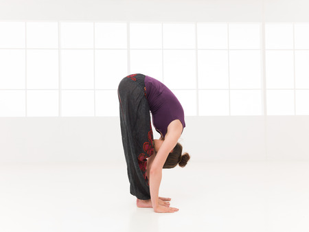 bending forward: forward bending yoga pose, shown by younf female, dreesed colorful, on white background, side view in studio