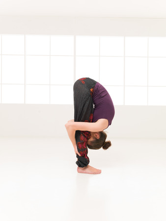 introversion: young woman in intermediate yoga pose, face between the legs, full body view