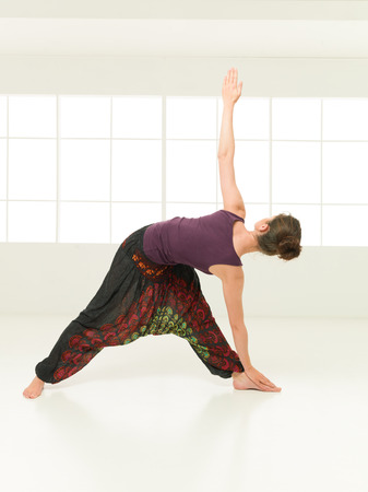 introversion: young woman in stretching yoga posture, dressed colorful on indor background Stock Photo