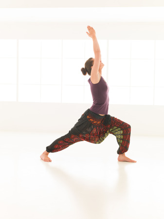 introversion: side view of single  women in yoga pose, dressed colorful on window background, face obscured