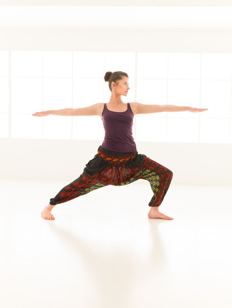 introversion: single young, woman in yoga pose, dressed colorful in studio light and reflection Stock Photo