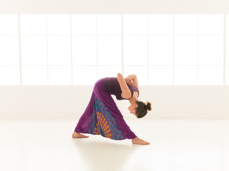 introversion: young,  woman practicing yoga posture, with face obscured, indor shot Stock Photo