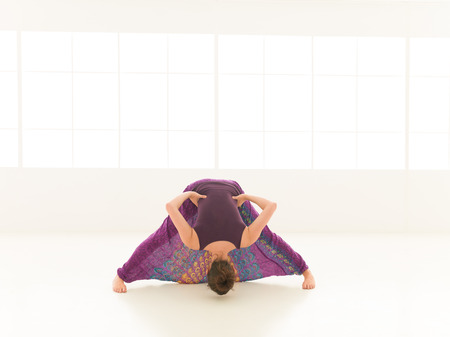 introversion: frontal view of stretching yoga posture, by young woman, colorful, iluminated window backgrond  Stock Photo