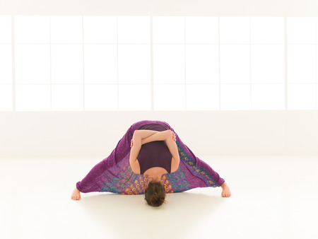 introversion: frontal view of difficult yoga pose demonstrated by young blonde female, dressed colorful, iluminated window backgrond  Stock Photo