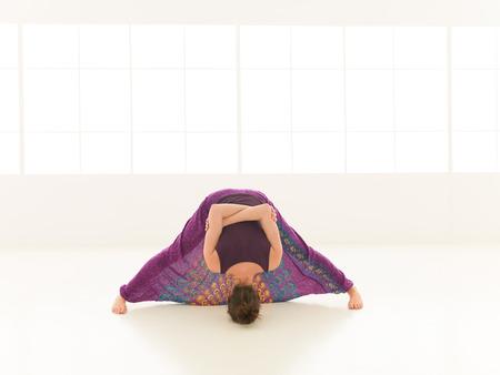 iluminated: vista frontal de dif�cil pose de yoga demuestra Hembra rubia joven, vestido colorido, backgrond ventana iluminated