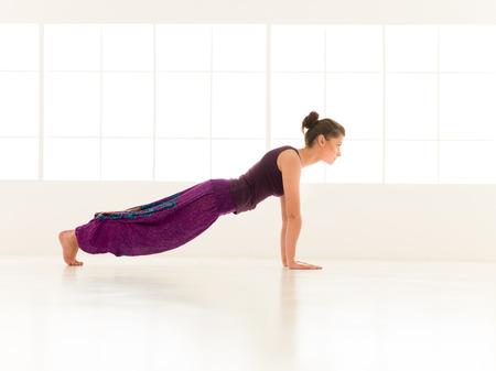 iluminated: vista lateral completa de la mujer joven que demuestra yoga equilibrar pose, vestido colorido, backgrond ventana iluminated Foto de archivo