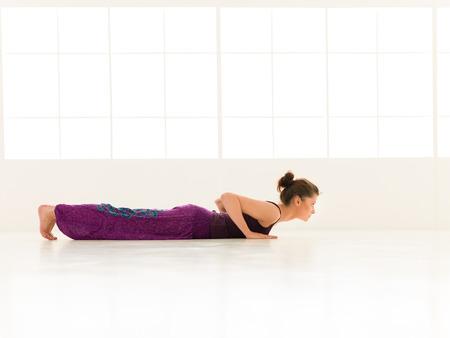 iluminated: mujer joven en el equilibrio pose de yoga, vista lateral, todo el cuerpo, vestido colorido, backgrond ventana iluminated
