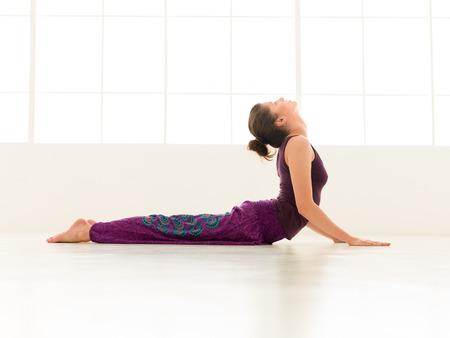 iluminated: mujer joven que demuestra dif�cil postura de yoga, la vista lateral de cuerpo entero, vestido colorido, backgrond ventana iluminated