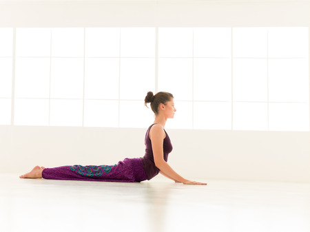 COBRA: young woman demonstrating difficult yoga posture, full body side view, dressed colorful, iluminated window backgrond  Stock Photo