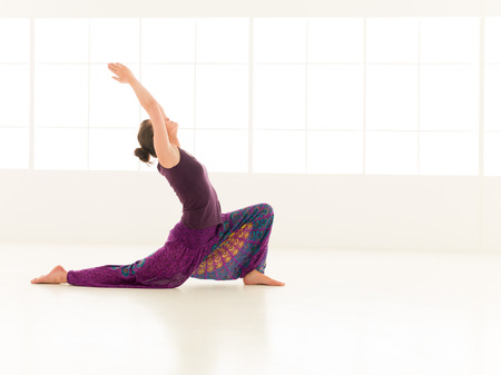 iluminated: vista lateral de la mujer que se sienta en postura de yoga, vestido colorido, backgrond ventana iluminated