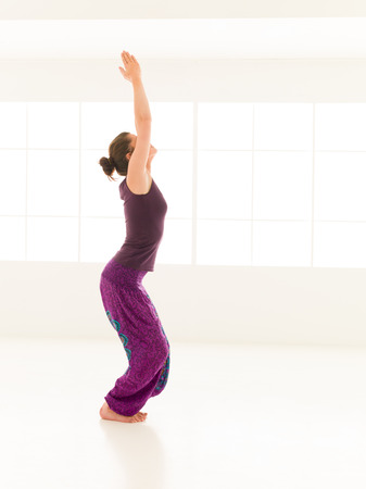 full body view of young woman demonstrating yoga pose, dressed colorful, iluminated window backgrond photo