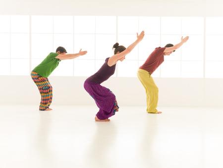 Three students performing Utkatasana studio light background window photo