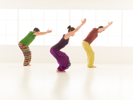 introversion: Three students performing Utkatasana studio light background window