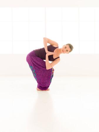 iluminated: mujer joven que demuestra yoga dif�cil plantear, vestido colorido, fondo de la ventana iluminated Foto de archivo
