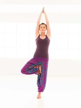 vriksasana: frontal view of young woman sitting in yoga posture, dressed colorful, iluminated window background