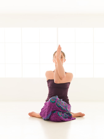 advanced yoga sitting posture by young female indor Stock Photo
