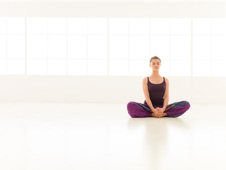 baddha: young girl , demonstrating yoga pose, full front view. Stock Photo