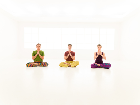 Three young people practice, yoga class photo