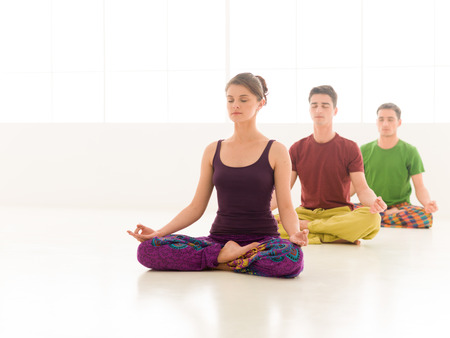 Three young people a woman and two men practice yoga class stand in line