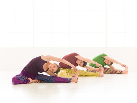 Drie jonge mensen een vrouw en twee mannen beoefenen yogales parivrtta janu sirsasana oefeningen, Stockfoto