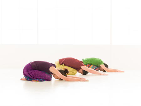 Three young people a woman and two men practice yoga in class on background window colorful